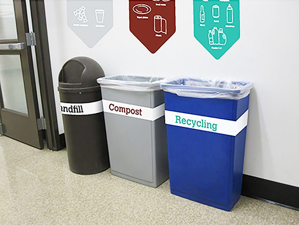 Three recycling bins are lined up against a wall